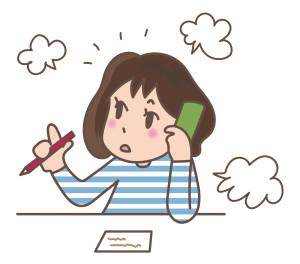 メモをとりながら電話する女性